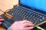 Hands operating a laptop with JAWS Screen Reader